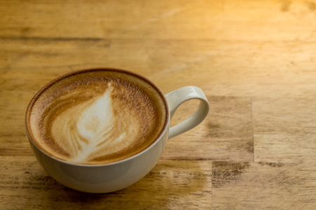 Cup of frothy cappucino on a wooden table with lots of room for copyspace.  This yummy and delicious creamy drink is part of your morning routine and helps you wake up.  Organic beans.