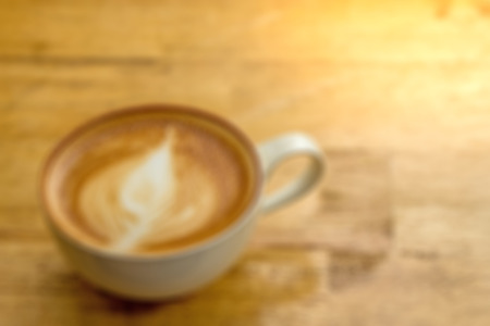 Blurred cup of creamy cappucino on wooden desk with lots of room for copyspace.  This yummy and delicious creamy drink is part of your morning routine and helps you wake up.  Organic beans. Stock Photo