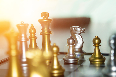 reflective: High exposure bright chess battle in business competition concept.  Two teams with only one victor in financial battle.  Investment and planning concept with copyspace. Stock Photo