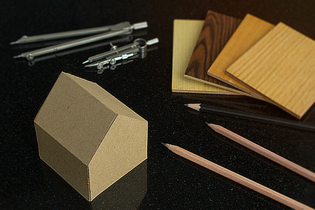 achitect samply materials for home design and construction concept with copy space.  pencils and protracters, house and wood grain samples with black background.