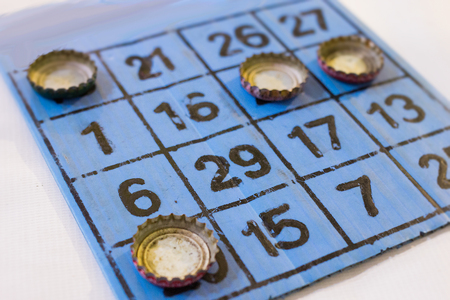 Bingo played with bottle caps.  Winners board with no skill or risk in this game.  White and blue.