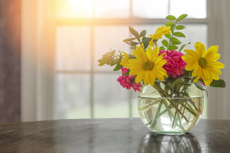 greys: Spring flowers on table in vase with dark greys and blacks with open window fresh concept and copyspace.