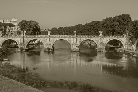 Old bridge in rome in sepia black and white for travel and tourism in europe and old ancient architecture concept with copyspace.
