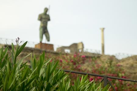 Wazig Pompeii-steenstandbeeld die ingang tot oude stad op heuveltop met groen in nadruk bewaken. Toerisme en reizen in Italië. Stockfoto