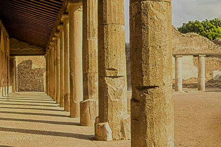 Tours of Europe and historical sites.  Pompeii.  Ancient pillars of strength concept with long evening shadows in historical tourism and travel location.
