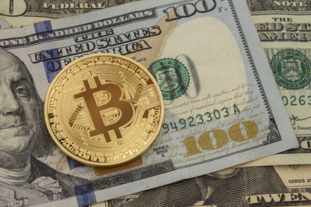 electronic commerce: Bitcoin and dollar.  BTC market symbol cryptocurrency rising above the united states dollar.  Gold metal bitcoin on top of paper currency.  Copy space for text and wording.