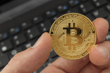 Holding a bitcoin digital currency with laptop in background.