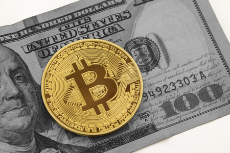 Golden bitcoin on black and white hundred dollar bill with white background.