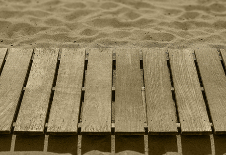 Empty board walk on sand in sepia ton with copy space.