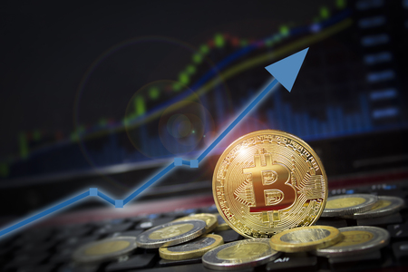 Bitcoin currency rising arrow price record highs on keyboard computer with golden bitcoin and other currencies.