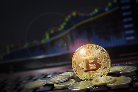 Cryptocurrency bitcoin with US dollar competition with candle chart in background.  Copyspace for words.