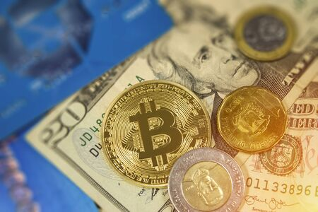 Bitcoin currency with dominican and american dollars and credit cards with light.  New high prices and investing your money in the market. Stock Photo