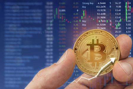 배경에서 노트북과 함께 bitcoin 디지털 통화를 들고. 스톡 콘텐츠