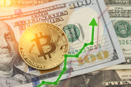 Bitcoin and dollar.  BTC market symbol cryptocurrency rising above the united states dollar.  Bitcoin on top of paper currency.  Copy space for text and wording.