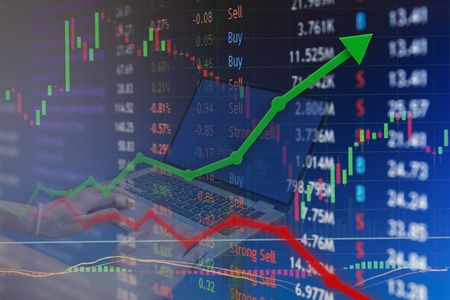 Home investing on laptop.  Stock market concept gain and profits with faded candlestick charts. Stock Photo