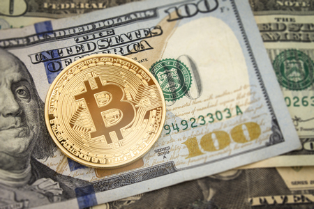 Bitcoin and dollar.  BTC market symbol cryptocurrency rising above the united states dollar.  Gold metal bitcoin on top of paper currency.  Copy space for text and wording.