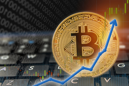 Bitcoin currency rising arrow price record highs on keyboard computer with golden bitcoin and other currencies. Stock Photo