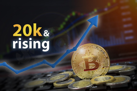 Bitcoin currency rising arrow price record highs on keyboard computer with golden bitcoin and other currencies. Stock fotó