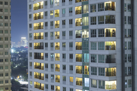 Residential apartment windows at night for electrical and power energy concept.  Individual living spaces and urban sprawl to highrise buildings. Editorial