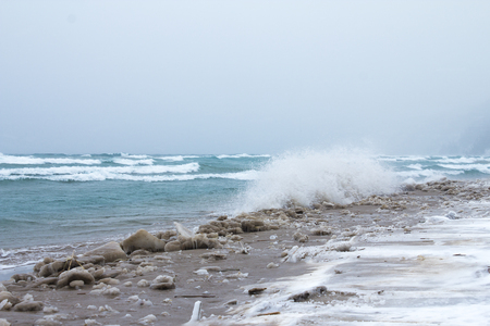 Aqua lake michigan in dead of winter with frozen ice chunks and powerful wind and waves.