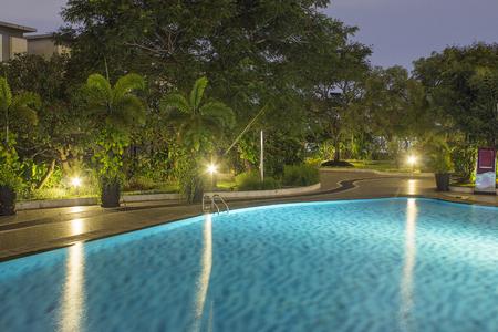 Piscine de nuit avec une végétation luxuriante et un éclairage pour la conception de la maison et l'aménagement paysager dans la cour. Ombres nocturnes et reflets sur l'eau de la piscine.