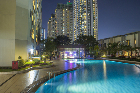 Condo and apartment complex planning and design with swimming pool in the city at night.  Blue waters and open clean design plan.