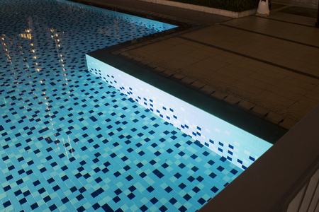 Sharp pool corners jagged design in blue tiles with shallow water in evening light concept. Stock Photo
