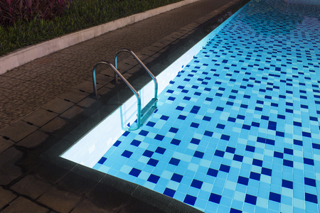Shallow blue pool lighting in evening for design and backyard deck planning for family space.
