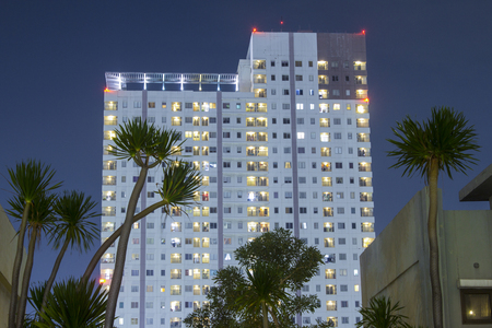 Apartment tower at night with trees in tropical city.  Urban planning and privacy conceptual photo for design and rental leasing company.