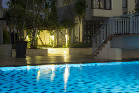 Warm blue lighting for swimming pool in the evening for family hangout area and backyard deck recreational pool. Stock Photo