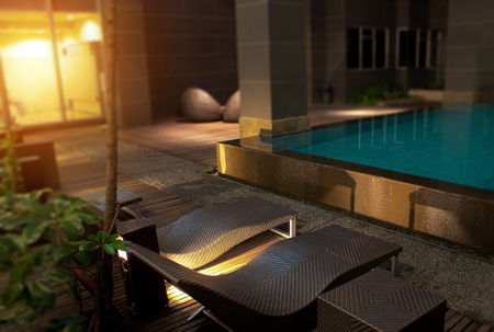 Romantic evening mood lighting casting shadows onto a romantic setting near the pool.  This luxury home has some of the best landscaped gardens and tropical flora in the world. Stock Photo