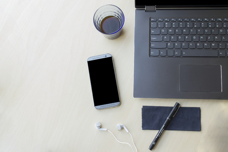 Grey laptop top-down view with phone and pen and coffee for home office business concept.