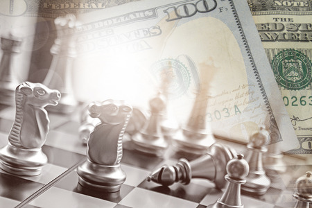 Business competition in chess battle with american dollars and money gain for capital gain.  Financial planning and investing.