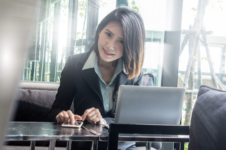 Asian business woman with laptop managing and planning as company CEO in ASEAN region.