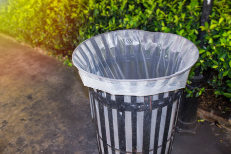 Blurred background with isolated trash can with bright light and green hedge in the evening for throw away waste concept and recycling. Stock Photo