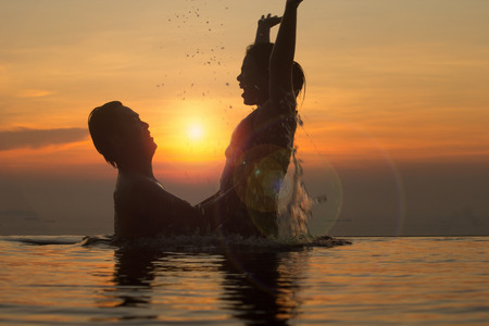 Faith and trust with strong warm feeling and emotional connection.  True love and romance with silhouette and sunset in background. Banque d'images