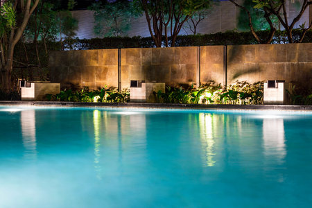 Lush pool lighting in backyard for luxury swimming pool design created by great lighting professionals. Redactioneel