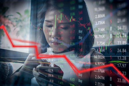 Falling stock prices and failure.  Financial loss with woman checking on mobile phone and trading options.
