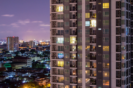 Apartment windows at night each with privacy in thier own home.  Real estate prices soaring in asian condos. Banco de Imagens