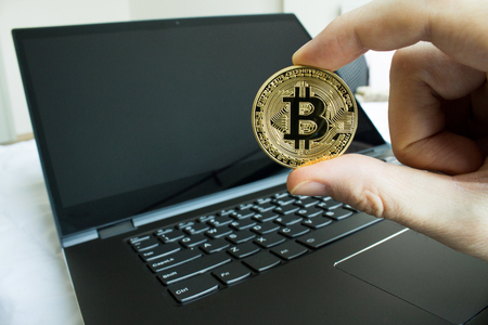 Holding a bitcoin investment for financial gain.  Hand holding a physical bitcoin. Stok Fotoğraf