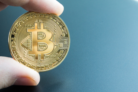 Holding a bitcoin investment for financial gain.  Hand holding a physical bitcoin. Stock Photo