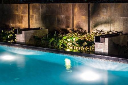 Zwembadverlichting in de achtertuin 's nachts voor gezinslevensstijl en woonruimte. Luxe design met goed licht en schoon landschap.