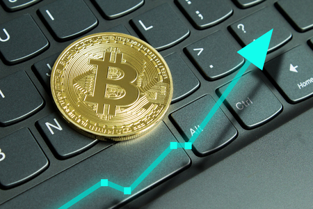 Bitcoin on computer laptop for investing and happiness for financial and business gain concept.  Green up arrow rising prices.