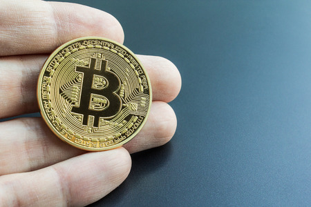Owning bitcoin investment symbolized by a hand holding a real bitcoin.  Buying and investing in BTC crypto-currency.