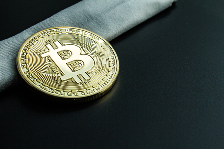 Learn how to invest on crypto exchange.  Physical golden bitcoin on white cloth.