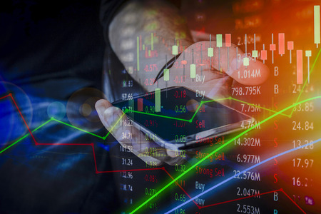 Hand pointing at mobile device for business use and charting data with bar charts and pie chart and valueable information on the company financial network.