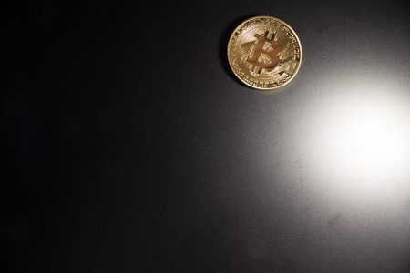 Isolated bitcoin on dark background with bright light and copy space for words. Zdjęcie Seryjne