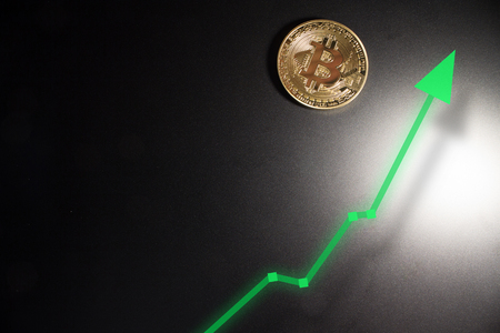 Bitcoin price and value increase on black background with white spotlight and green increase arrow.  Rising prices of crypto. Zdjęcie Seryjne