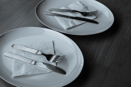 Plates set on table with silverware and white napkins and white dishware plates with wooden table top.  restaurant and cooking for chef website.