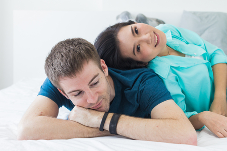 Couple with good communication skills.  White background laying on bed and happy.